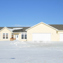 yellow house in winter with three car garage