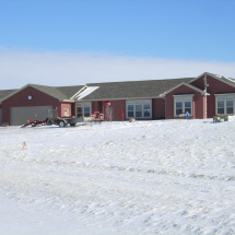 custom home in winter with snow and garage